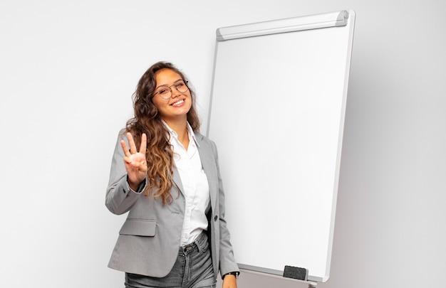 Jovem empresária sorrindo e parecendo amigável, mostrando o número três ou terceiro com a mão para a frente, em contagem regressiva