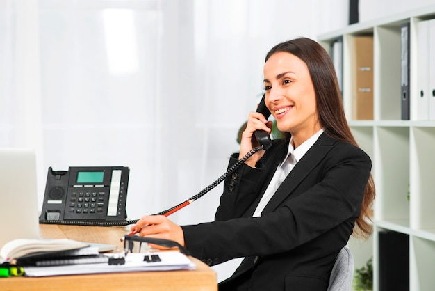 Jovem empresária sorrindo enquanto fala no telefone no escritório