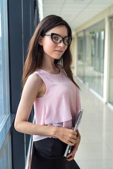 Jovem empresária sozinha com o bloco de notas em pé no centro de negócios. pausa para o café