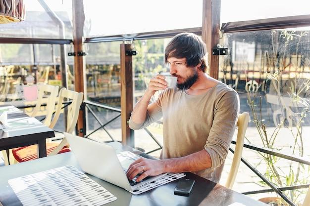 Jovem empresária tomando café e usando computador tablet no café