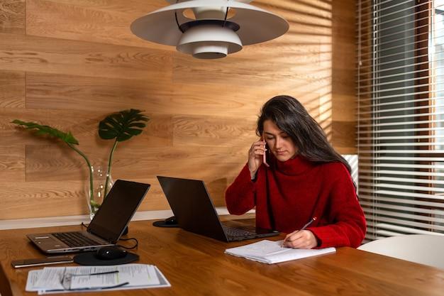 Jovem empresária tomando notas enquanto fala ao telefone em sua estação de trabalho na frente de seu laptop