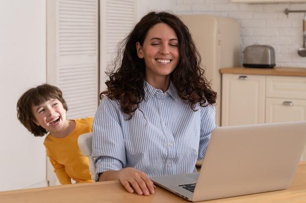 Jovem empresária trabalha como freelance ou remotamente do escritório em casa com o filho brincalhão