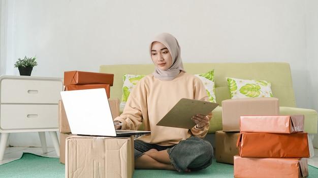 Jovem empresária trabalhando com laptop na sala