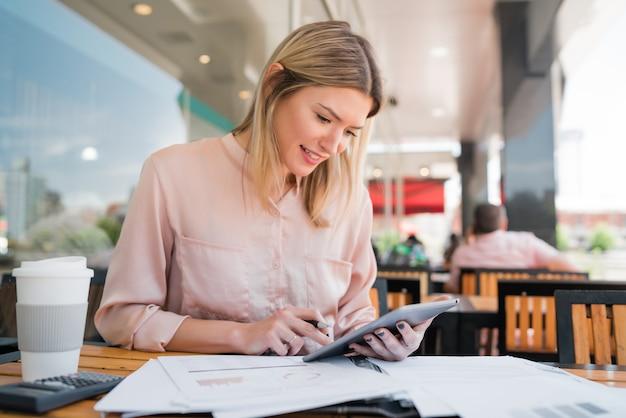 Jovem empresária trabalhando com um tablet digital.
