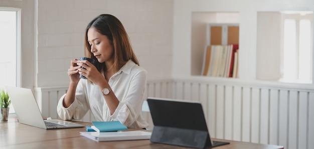 Jovem empresária trabalhando em seu projeto e bebendo uma xícara de café no escritório moderno