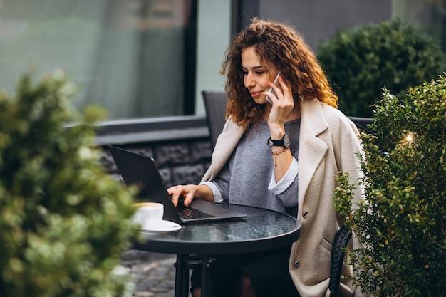 Jovem empresária trabalhando em um computador fora do café