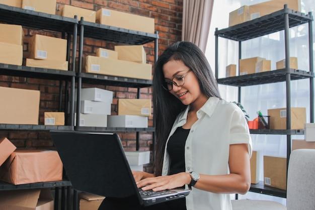 Jovem empresária usando laptop trabalha em casa