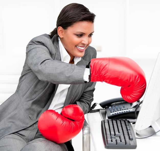 Jovem empresária usando luvas de boxe, socando um computador