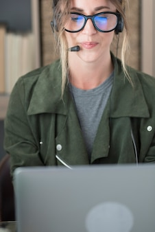 Jovem empresária usando óculos e fone de ouvido enquanto usa o laptop no local de trabalho, linda mulher usando o laptop. mulher usando fone de ouvido com microfone, olhando para a tela do laptop