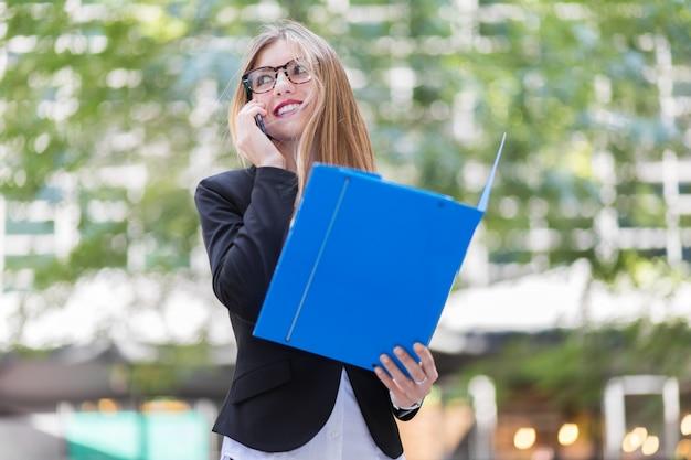 Jovem empresária usando óculos e lendo documentos ao ar livre