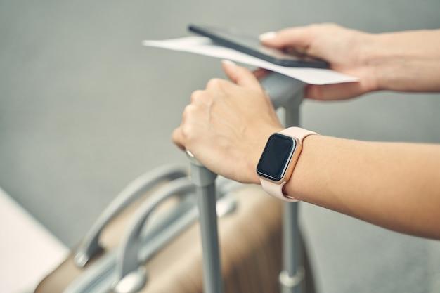 Jovem empresária usando relógios inteligentes e segurando o telefone com o bilhete na mão direita