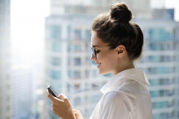 Jovem empresária usando smartphone em seu escritório