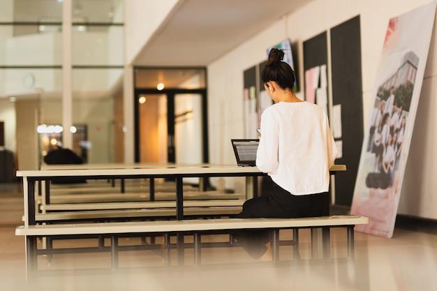 Jovem empresária usando telefone celular com o laptop aberto na mesa.