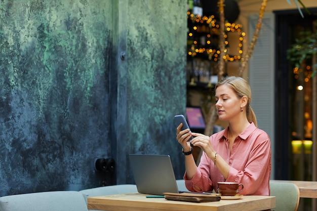 Jovem empresária usando telefone celular enquanto está sentada à mesa com o laptop e trabalhando no café
