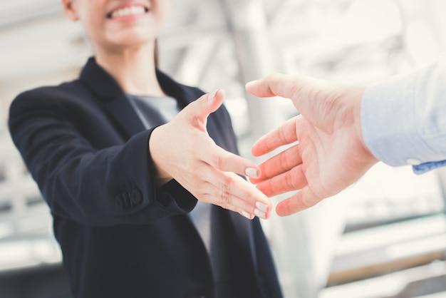 Jovem empresária vai fazer aperto de mão com um empresário
