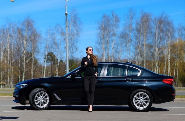 Jovem empresária vestida de preto com um carro caro