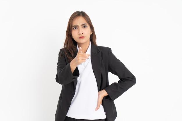Jovem empresária vestindo terno apontando para a câmera com expressão séria