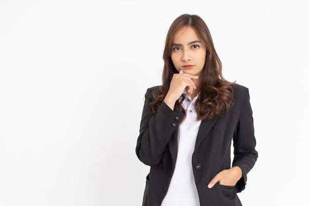Jovem empresária vestindo um terno preto pensando seriamente com a mão segurando o queixo com copyspace
