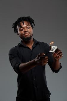 Jovem empresário africano bem sucedido, queimando dinheiro no escuro