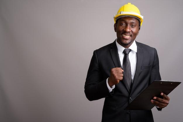 Jovem empresário africano bonito com capacete contra bac cinza