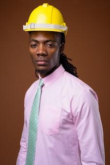 Jovem empresário africano bonito com capacete de segurança contra o fundo marrom