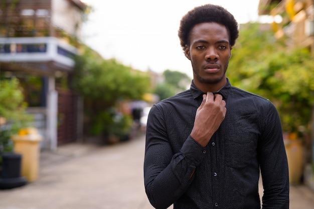Jovem empresário africano bonito na rua ao ar livre
