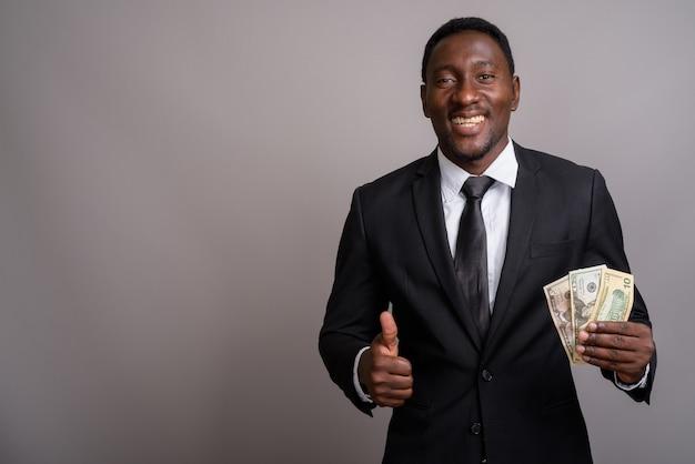 Jovem empresário africano bonito segurando dinheiro e sorrindo