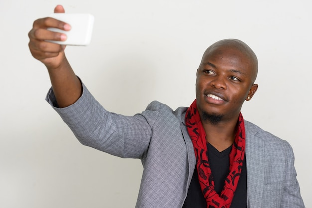 Jovem empresário africano careca feliz tirando uma selfie
