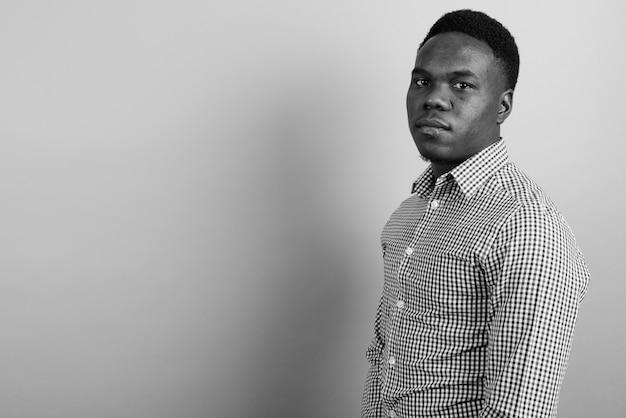 Jovem empresário africano com cabelo afro contra uma parede branca. preto e branco Foto Premium