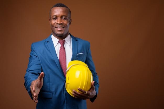 Jovem empresário africano com capacete de segurança contra um fundo marrom
