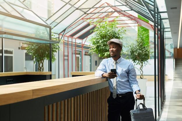 Jovem empresário africano com mala usando seu telefone celular enquanto está na sala de espera