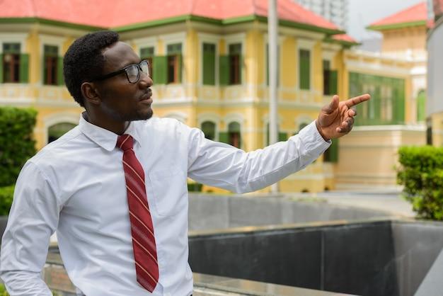 Jovem empresário africano com óculos apontando o dedo nas ruas da cidade ao ar livre