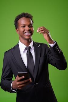Jovem empresário africano contra parede verde