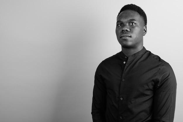 Jovem empresário africano contra uma parede branca. preto e branco