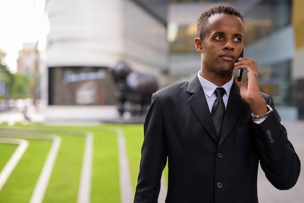 Jovem empresário africano de sucesso falando ao telefone ao ar livre