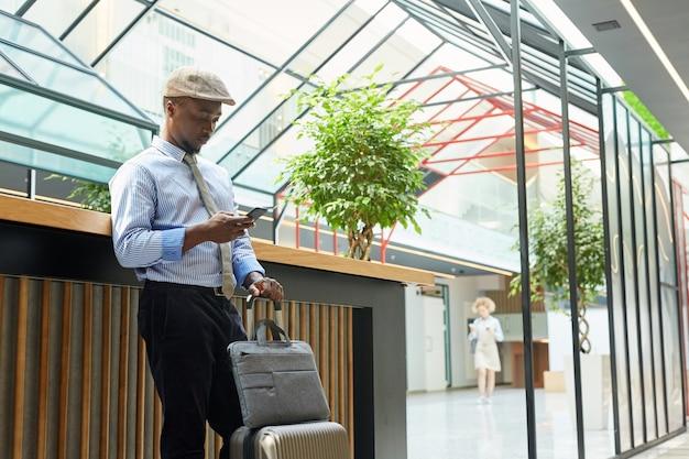 Jovem empresário africano em pé com uma mala e usando seu telefone celular