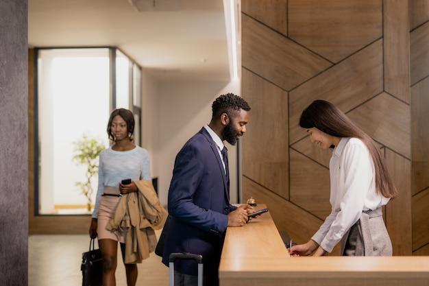 Jovem empresário africano em trajes formais, curvado sobre o balcão da recepção no saguão do hotel enquanto fala com a recepcionista