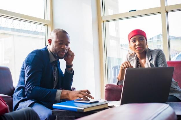 Jovem empresário africano fazendo uma ligação enquanto seu colega espera por ele.