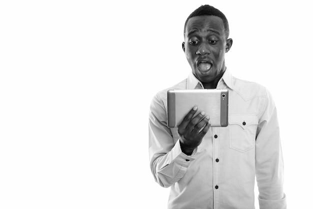 Jovem empresário africano isolado contra uma parede branca em preto e branco
