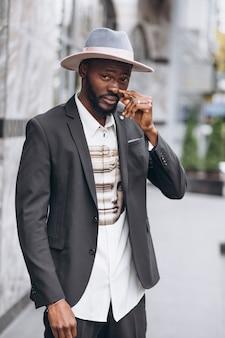 Jovem empresário africano no cigarro de fumo de terno elegante