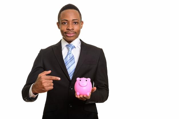 Jovem empresário africano segurando o cofrinho e apontando