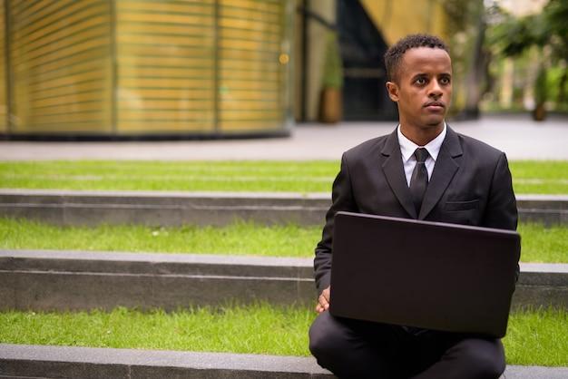 Jovem empresário africano sentado e usando um laptop ao ar livre