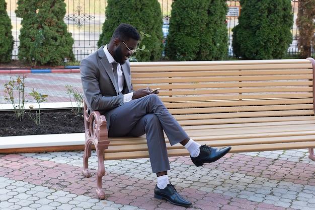 Jovem empresário africano sorrindo no banco da cidade com um telefone, tablet