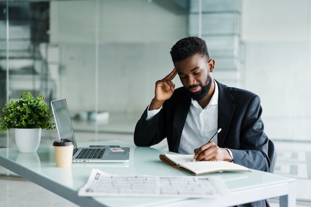 Jovem empresário africano trabalhando no escritório, no laptop e fazer aviso no notebook