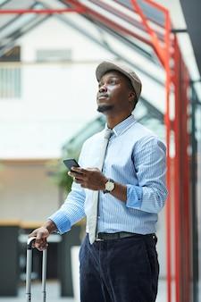 Jovem empresário africano usando seu telefone celular enquanto está com uma mala no aeroporto, ele tem uma viagem de negócios