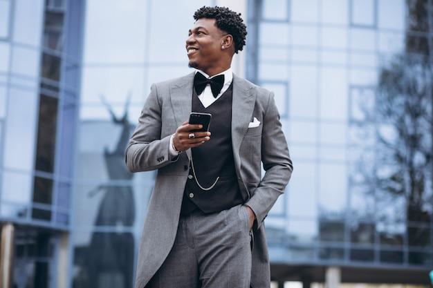 Jovem empresário africano usando telefone