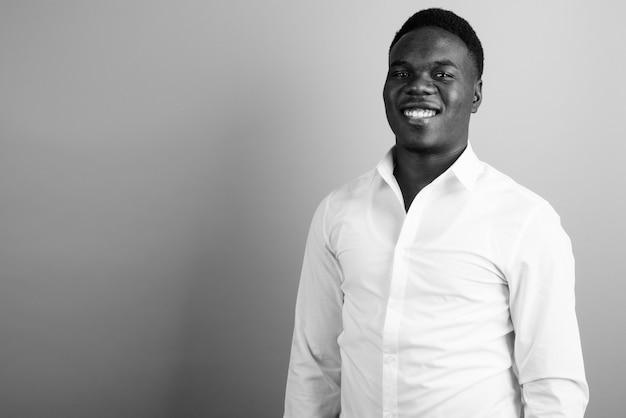 Jovem empresário africano vestindo camisa branca contra uma parede branca. preto e branco