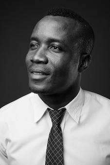 Jovem empresário africano vestindo camisa branca e gravata contra uma parede cinza. preto e branco