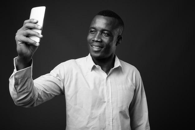 Jovem empresário africano vestindo camisa contra uma parede cinza. preto e branco