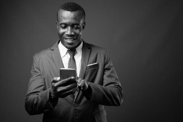Jovem empresário africano vestindo terno contra parede cinza. preto e branco